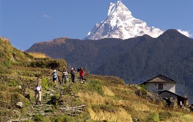people trekking by house